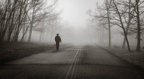 Ein Mann geht allein in den gespenstischen Nebel Lizenzfreies Stockfoto