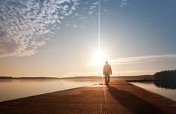 Ein Mann geht auf den Pier im Sonnenaufgang Lizenzfreies Stockbild