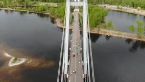 Ein Mann geht auf ein Seil, das zwischen die Unterstützungen der Brücke an der großen Höhe ausgedehnt wird stock video