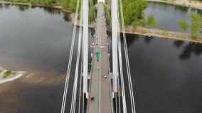 Ein Mann geht auf ein Seil, das zwischen die Unterstützungen der Brücke an der großen Höhe ausgedehnt wird stock footage