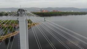 Ein Mann geht auf ein Seil, das zwischen die Unterstützungen der Brücke an der großen Höhe ausgedehnt wird stock video footage