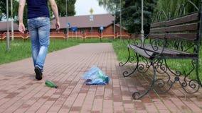 Ein Mann geht durch die Stadt und wirft heraus ein Paket des Abfallrechtes auf dem Weg im Park, ein Abfall in der Stadt stock video footage