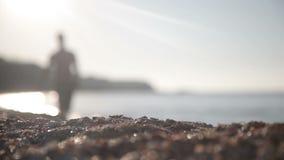 Ein Mann geht entlang die Küste stock footage