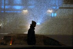 Ein Mann geht unter starken Schneefälle Stockfoto
