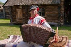 Ein Mann, gekleidet in einem russischen Volkskostüm, spielt das Akkordeon stockfotografie
