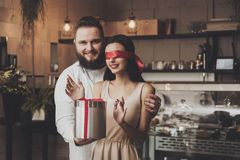 Ein Mann gibt einem Mädchen mit geschlossenen Augen ein Geschenk stockfoto
