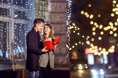 Ein Mann gibt seiner Freundin einen Kasten mit einem Geschenk draußen stockfotografie