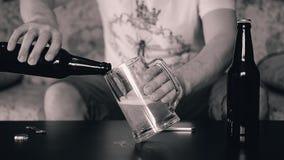 Ein Mann gießt aus einer Flasche in einen großen Bierkrug Einfarbige Farbe Warmer Ton stock video footage