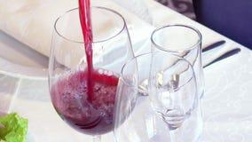 Ein Mann gießt ein Glas Rotwein stock video