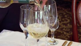 Ein Mann gießt ein Glas Weißwein stock video footage