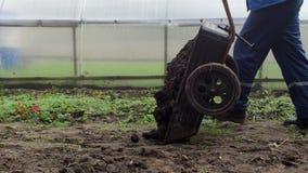 Ein Mann gießt einen Gartenwarenkorb mit Düngemittel, um den Boden im Garten, Landhäuschenbereich, Mist zu befruchten stock video footage