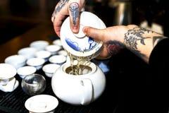 Ein Mann gießt Tee während einer Teezeremonie Lizenzfreie Stockbilder