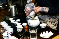 Ein Mann gießt Tee während einer Teezeremonie Lizenzfreie Stockfotos
