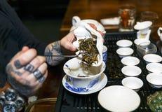 Ein Mann gießt Tee während einer Teezeremonie Lizenzfreies Stockfoto