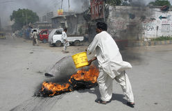 Ein Mann gießt Wasser über Feuer Lizenzfreies Stockbild