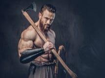 Ein Mann hält Axt über dunkelgrauem Hintergrund lizenzfreies stockfoto