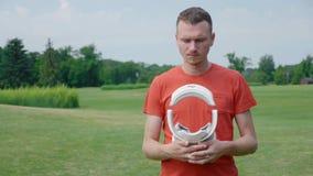 Ein Mann hält in den Händen einen VR-Kopfhörer im Park stock video