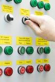 Ein Mann hält die Hand des Hauptschalters des elektrischen Kabinetts Stockbilder