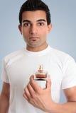 Ein Mann hält eine Flasche Cologne an Lizenzfreies Stockfoto