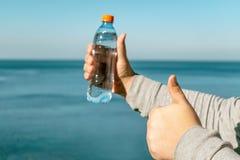 Ein Mann hält eine Plastikflasche Trinkwasser in seiner Hand und steht auf dem Ozean stockfotografie