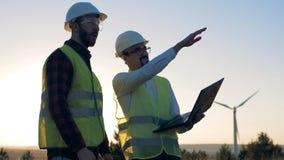 Ein Mann hält einen Laptop in den Händen und in einen anderen Ingenieurpunkten auf Windkraftanlagen Umweltenergiekonzept stock video