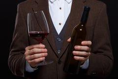 Ein Mann hält ein Glas des Weins und der Flasche auf einem schwarzen Hintergrund Stockbilder