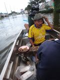 Ein Mann hält, Lebensmittel zu genießen und trinkt in seinem Boot in einer überschwemmten Straße von Pathum Thani, Thailand, im O stockfotografie