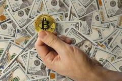 Ein Mann hält in seiner Hand, die eine Münze eines cryptomoney Münze bitcoin biss Stockbilder