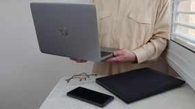 Ein Mann in hellfarbigem offiziellem Hemd steht in der Ecke nahe Fenster stockfotos