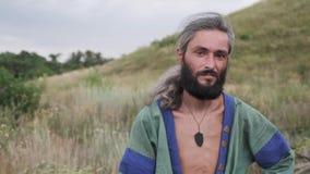 Ein Mann im ethnischen Kostüm steht auf einem Gebiet und schaut weg durchdacht stock video