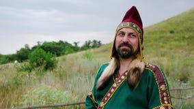 Ein Mann im ethnischen Kostüm steht und schaut weg durchdacht stock video footage