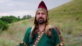 Ein Mann im ethnischen Kostüm steht und schaut weg durchdacht Langsame Bewegung stock video footage