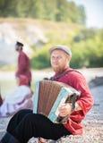 Ein Mann im russischen nationalen Kostümstand auf dem Hintergrund einer erstaunlichen Landschaft, die Akkordeon spielt stockfotos