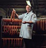 Ein Mann im Wurstspeicher Lizenzfreie Stockfotografie