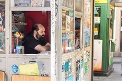 Ein Mann, Inhaber eines hölzernen Zeitungskiosks, Wartekunden am La Coruña, Spanien lizenzfreie stockfotografie