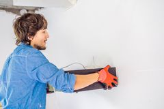 Ein Mann installiert ein elektrisches Gerät auf eine Wand in eine neue Wohnung stockfotos