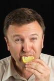 Ein Mann isst eine Zitrone Stockbild