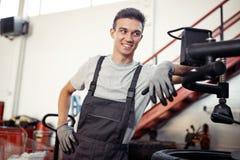 Ein Mann ist bei seiner Arbeit in einem Autoreparaturservice während eines Bruches lizenzfreies stockfoto