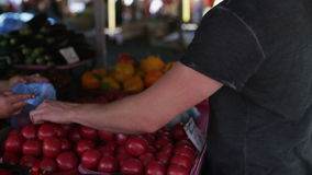 Ein Mann kauft Gemüse an einem Markt der Tag stock video footage