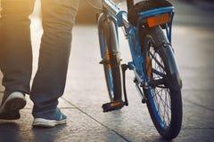 Ein Mann, kleidete blaue Turnschuhe, tr?gt ein blaues Fahrrad lizenzfreie stockfotografie