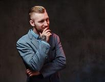 Ein Mann kleidete in einer Klage über grauem Hintergrund an Lizenzfreie Stockbilder
