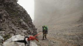 Ein Mann klettert einen Berg, der ein Seil, Zeitlupe hält stock footage