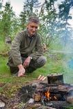 Ein Mann kocht Würste auf dem Feuer lizenzfreie stockfotografie
