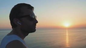 Ein Mann läuft entlang das Ufer und spielt Sport bei Sonnenuntergang H?rende Musik des Athleten Athlet Using Wireless Earphones stock footage