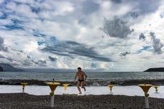 Ein Mann läuft entlang die Küste Stockbilder