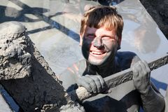 Ein Mann lacht während aufwärts in einem therapeutischen Schlammsee Lizenzfreies Stockfoto