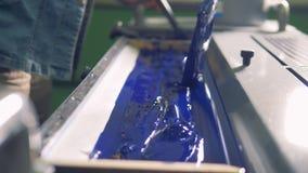 Ein Mann legt starke blaue Farbe in einer speziellen Einheit einer Fabrikdruckmaschine stock footage