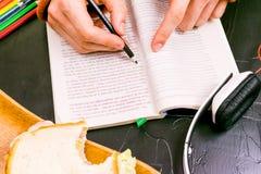 Ein Mann liest, übersetzt den Text Sandwich, Kopfhörer, Bleistifte, Notizbücher Stillleben, schwarzer Hintergrund Lizenzfreies Stockbild