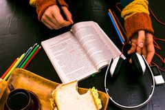 Ein Mann liest, übersetzt den Text Sandwich, Kopfhörer, Bleistifte, Notizbücher Stillleben, schwarzer Hintergrund Stockfotografie