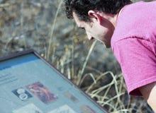 Ein Mann liest ein Zeichen bei Murray Springs Clovis Site Lizenzfreie Stockfotos